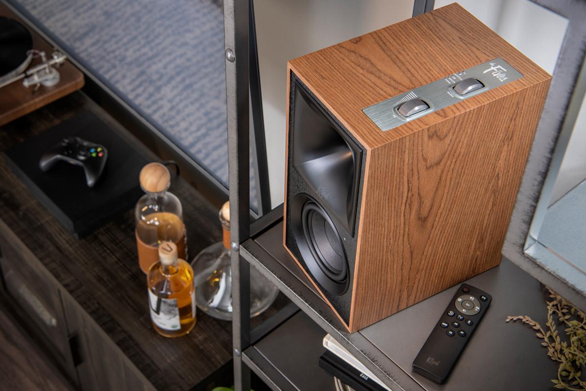 Top view of Klipsch the Fives walnut speaker next to Klipsch the Fives IR Remote